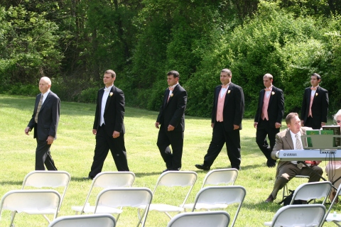The bridegroom and his men enter from the wooded thicket beside the grassy field.